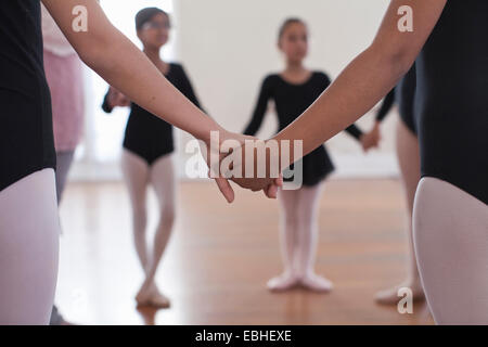 Rear view of a group of ballet school girls holding hands - Stock Photo