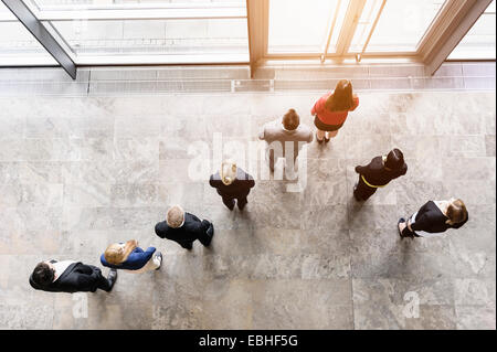 Overhead view of business team looking out of office window - Stock Photo