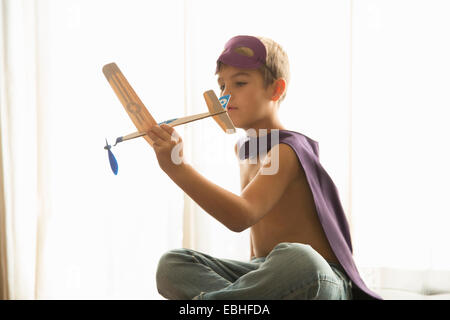 Boy in cape and mask playing with toy plane at home - Stock Photo