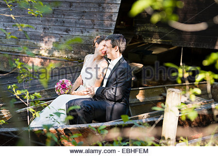 Bride and bridegroom sitting in rowing boat on river - Stock Photo