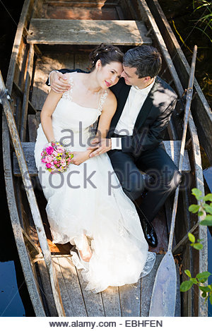 High angle view of bride and bridegroom sitting in rowing boat on river - Stock Photo