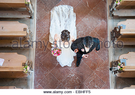 Overhead view of bride and bridegroom walking down the aisle in church - Stock Photo