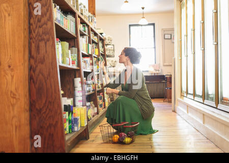 Female customer crouching whilst shopping in country store - Stock Photo