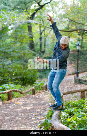Man balancing on garden edging - Stock Photo