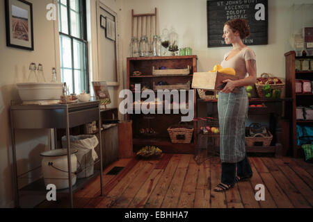 Female shop assistant carrying fruit and veg crate in country store - Stock Photo