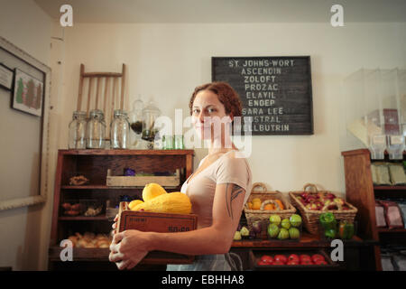Portrait of female shop assistant carrying fruit and veg crate in country store - Stock Photo
