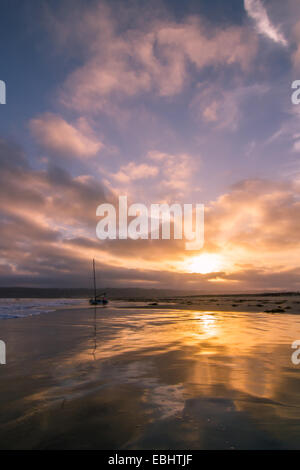 A stunning sunset over a sailboat reflected in the surf of Coronado Island near San Diego, California - Stock Photo