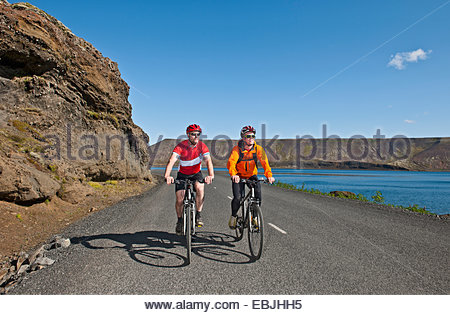 Cyclists cycling on road next to Kleifarvatn, Reykjanes, South West Iceland - Stockfoto