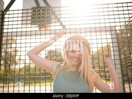 Portrait of young female basketball player holding onto wire fence - Stock Photo