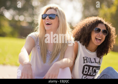 Two young female friends laughing in park - Stockfoto