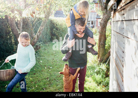 Father with daughter on shoulders in garden - Stock Photo