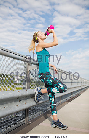Young woman drinking water from bottle - Stock Photo
