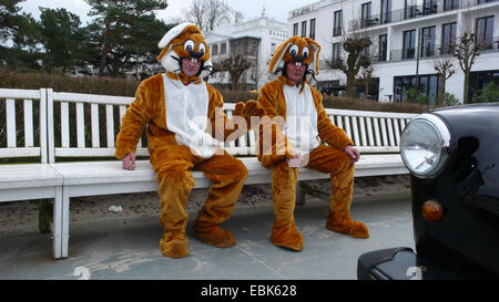 two men in Easter bunny costumes taking a break sitting on a bench with the masks opened, Germany, Mecklenburg-Western - Stock Photo