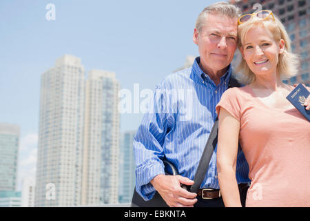 USA, New Jersey, Portrait of couple with passport against skyscrapers - Stock Photo