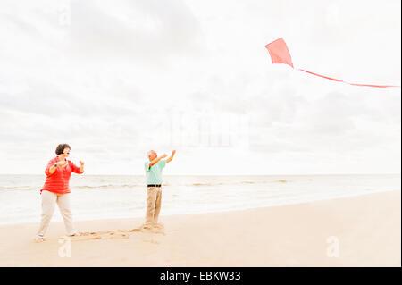 USA, Florida, Jupiter, Couple flying kite together on beach - Stock Photo