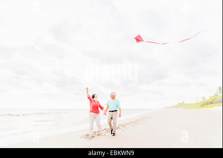 USA, Florida, Jupiter, Couple flying kite together on beach - Stock Photo