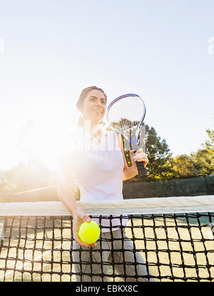 USA, Florida, Jupiter, Portrait of young woman standing by net, holding tennis ball and tennis racket - Stock Photo