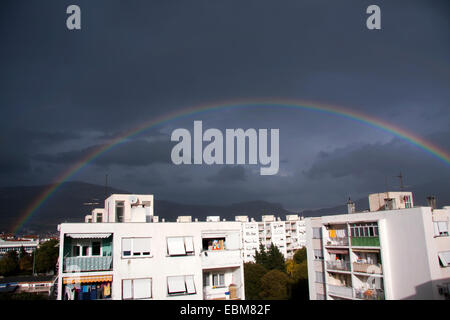 Rainbow over the city buildings on dark blue cloudy sky - Stock Photo