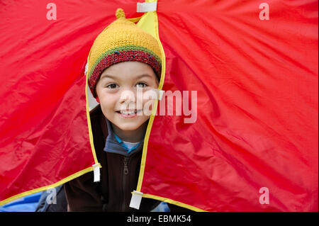 Boy with a knited cap looking out of a red tent, happy, Germany - Stock Photo