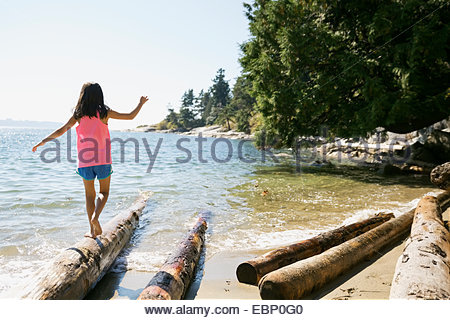 Girl balancing on driftwood at beach - Stock Photo