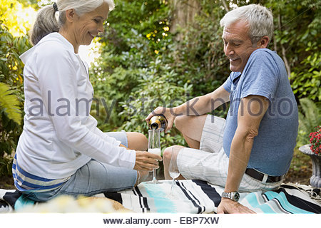 Senior couple drinking champagne on patio - Stock Photo