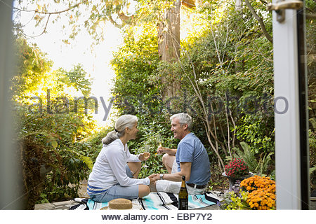 Couple drinking champagne on patio - Stock Photo
