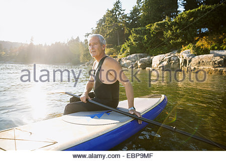 Senior man sitting on paddle board in ocean - Stock Photo