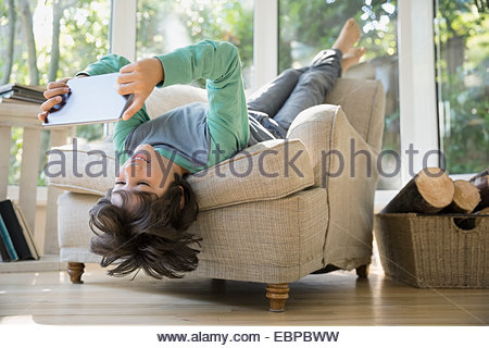 Boy using digital tablet upside-down in armchair - Stock Photo