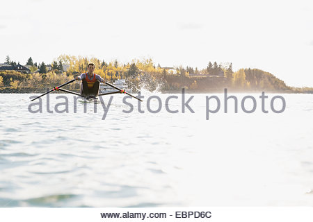 Rower in scull on sunny river - Stockfoto