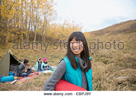 Smiling woman camping with family - Stock Photo
