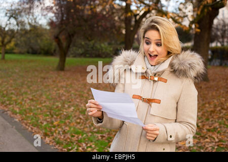 surprised woman reading a letter - Stock Photo