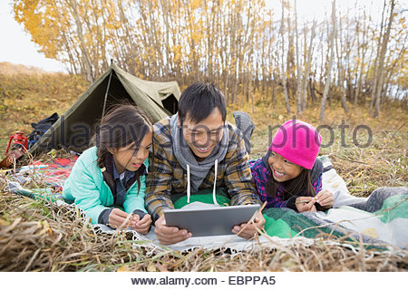 Father and daughters using digital tablet at campsite - Stock Photo