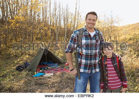 Portrait of father and son outside tent - Stock Photo