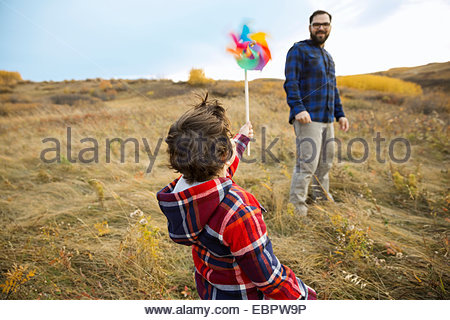 Father watching son with pinwheel in rural field - Stock Photo