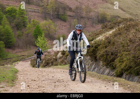 Cyclists cycling up a track on the north side of Jaggers Clough, Derbyshire, Peak District, England, UK - Stock Photo