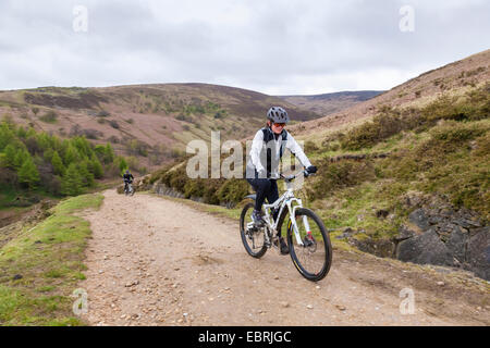 Woman cycling up the stony track on the north side of Jaggers Clough, Derbyshire, Peak District, England, UK - Stock Photo