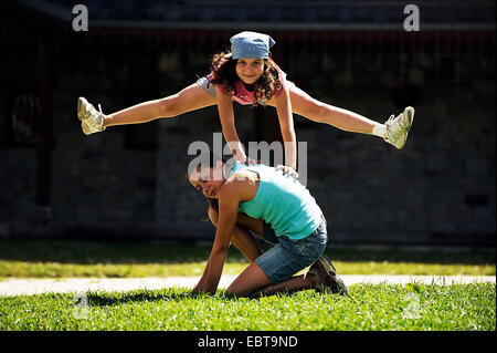 two girls leapfrogging on a lawn, France - Stockfoto