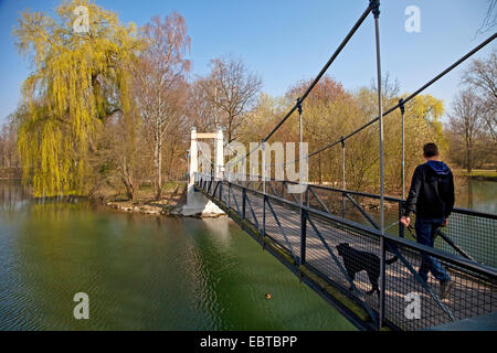 man with dog walking on the pedestrian bridge 'Mattenklodtsteg' over river Lippe , Germany, North Rhine-Westphalia, - Stock Photo