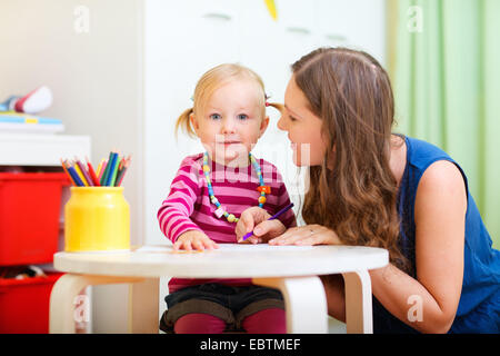 young mother sitting at the table with her little daughter drawing together - Stock Photo