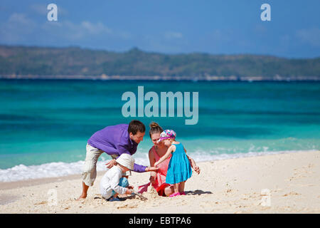 young family with two children playing on sandy beach - Stockfoto