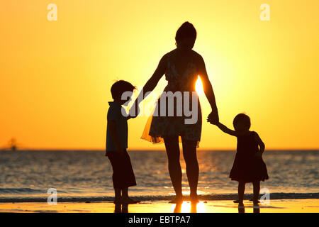 silhouettes of a mother and her two children on beach at sunset - Stock Photo