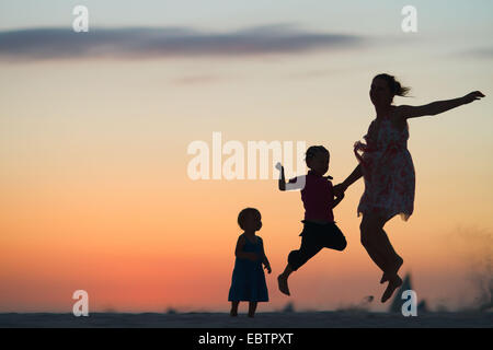 silhouettes of mother and two children jumping on beach at sunset - Stock Photo
