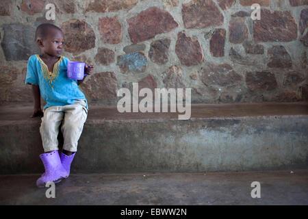 little boy with purple cup and purple rubber boots, Burundi, Bujumbura - Stock Photo