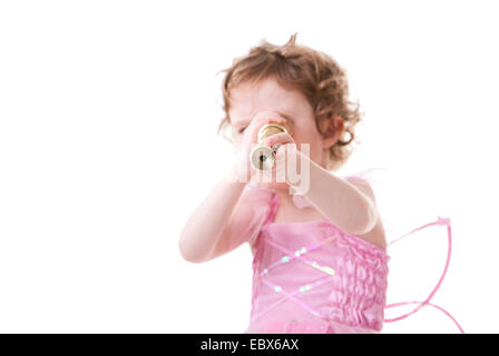 Cute curly haired girl in little fairy dress looking to telescope - Stock Photo
