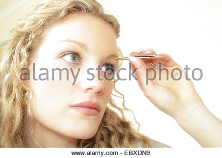 woman is picking her eyebrows - Stock Photo