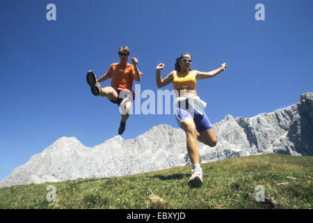 A couple is running over a mountain meadow. The man is doing an air jump - Stock Photo