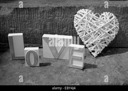 Wooden Love sign with wicker heart - Stock Photo