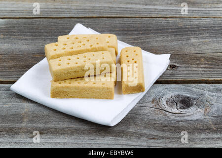 Close up horizontal image of butter cookies on white cloth napkin with rustic wood underneath - Stock Photo