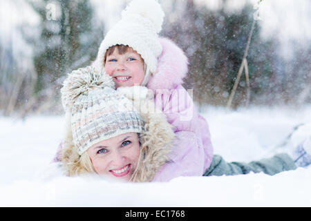Happy parent and kid playing with snow in winter outdoor - Stock Photo