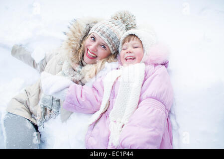 Happy mother and child have fun on snow in winter outdoor - Stock Photo